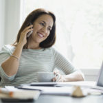 Smiling businesswoman using smart phone in home office